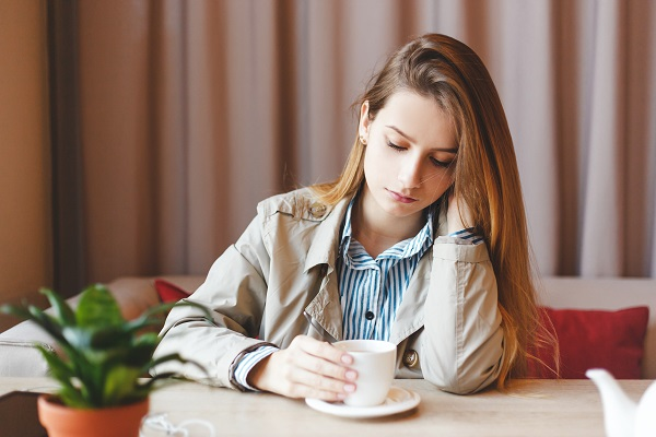 Young unemployed Ukrainian woman sits alone heartbroken at a coffee shop