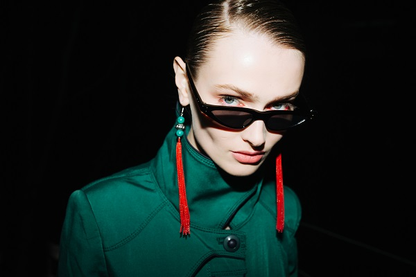 Young Ukrainian woman in fashionable sunglasses and red earrings confidently looking in the camera at night