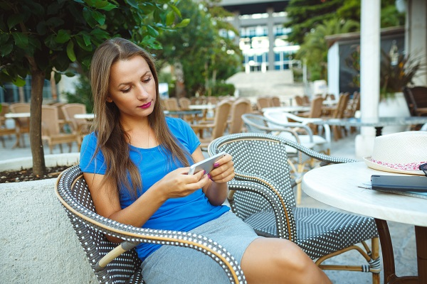 Young Ukrainian woman relaxing in the outdoor cafe and using her smartphone