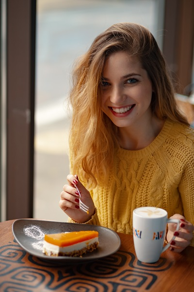 Young smiling attractive Ukrainian woman enjoying a cup of coffee and a slice of delicious cake