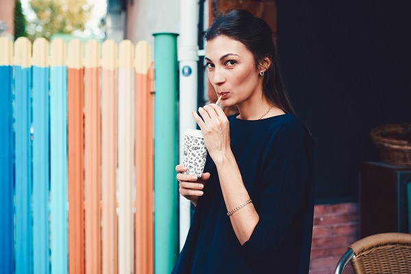 Fashionable pretty Ukrainian woman walking through the streets of a city drinking a cocktail