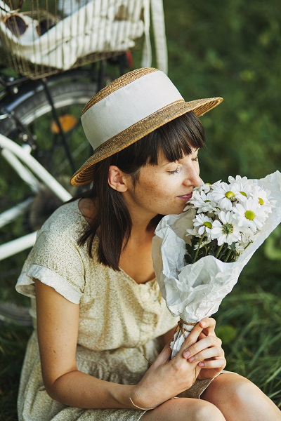 Outdoor portrait of an attractive young brunette Ukrainian woman in a hat on a bicycle
