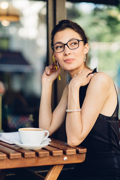 The photo on an attractive smiling young Ukrainian girl wearing glasses sitting with a cup of coffee