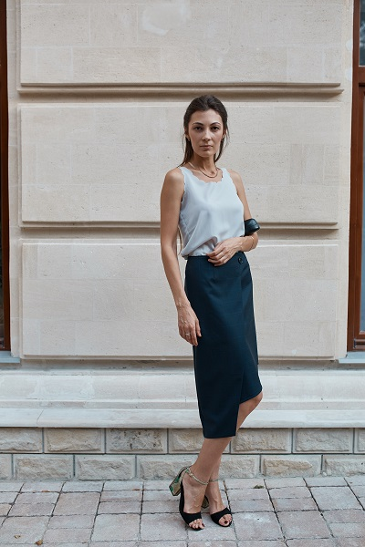 Serious adult charming Ukrainian woman wearing a long black skirt posing on the street of a city